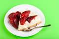 Strawberry cheesecake a delicious in a white plate on a green background Stock Photos