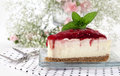 Strawberry cheesecake a slice of on square glass plate with dessert forks and flowers blurred in background a concept for Stock Photo