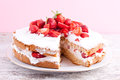 Strawberry cream cake on a white wooden table Stock Images