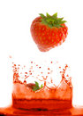 Strawberry falling in juice. Royalty Free Stock Image