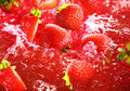 Strawberry falling into the lot of juice Royalty Free Stock Photos