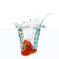 Strawberry falls deeply under water with a splash Stock Photos