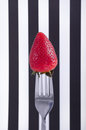 Strawberry on fork a a against a black and white stripped background for a modern art look Stock Photo