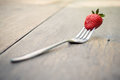 Strawberry on a fork selective focus over wooden table filter vintage style picture Royalty Free Stock Images