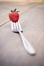 Strawberry on a fork selective focus over wooden table filter vintage style picture Royalty Free Stock Photography