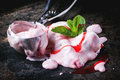 Strawberry ice cream close up of melting with fresh mint and metal spoon over black table Royalty Free Stock Images