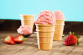 Strawberry ice cream on wood in waffle cones with a scoop in background Stock Photo