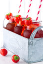 Strawberry juice with frozen icecubes and straws glasses of red striped in a metal vintage container Stock Photo