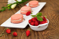 Strawberry macaroons closeup of a row of french with fresh alpine strawberries Stock Photo