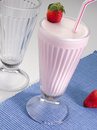 Strawberry milkshake with straw on a table setting Royalty Free Stock Photography