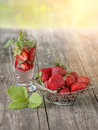Strawberry openwork vase in the background of the glass with a strawberry drink on wooden table on a Sunny day. The