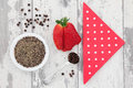 Strawberry and pepper fruit with peppercorns red polka dot serviette over distressed white wooden background Stock Images