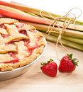 Strawberry rhubarb pie homemade with strawberries and on a wooden cutting board traditional late summer early fall dessert Stock Image