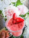 Strawberry smoothie in the hand of a girl. Woman drinking a pink cocktail with berries, a cocktail against the