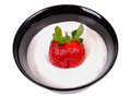 Strawberry with sour cream in a black bowl on white Royalty Free Stock Image