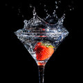 Strawberry splashing into glass of martini Royalty Free Stock Photo