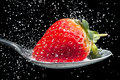 Strawberry sprinkled with sugar close up on a spoon pouring over it frozen high speed photography Stock Photos