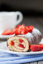 Strawberry swiss roll homemade cake with cream and a cup of tea on a wooden background selective focus Royalty Free Stock Photo