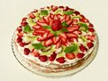 Strawberry tart cake with cream filling covered with strawberries kiwi and mint green and almonds close to Royalty Free Stock Photography