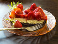 Strawberry tart cake with cream filling on a glass plate with folk