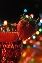 Strawberry on wineglass beverage in with a colorful festive christmas light bokeh background Stock Photography