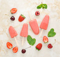 Strawberry yogurt ice cream popsicles with mint and cherry over Royalty Free Stock Photo
