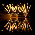 Streaks of golden fireworks reflected in a murky lake Stock Images