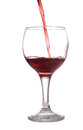 Stream of red wine flows in a wineglass isolated on white Stock Images
