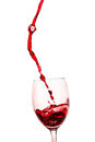 The stream of red wine poured into a glass Royalty Free Stock Photos
