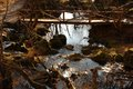 Stream and wooden bridge water between rocks with green moss small across Stock Photo