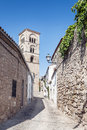 Street with arab tower cobbled located in the spanish village of trujillo even a side stone facades it is an upright image on a Stock Images