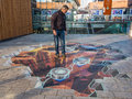 Street art showing optical illusion almere netherlands oct unknown man shows the power of d of a painting by an unknown artist Stock Photography