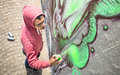 Street artist painting colorful graffiti on generic wall Royalty Free Stock Photo