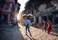 Street in bhaktapur kathmandu valley nepal april nepali man carrying tray with food and walking down the with shops Royalty Free Stock Photos