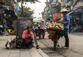 Hanoi Asian Street Business. Shoe cleaner and vegetable hawker.