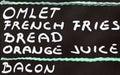 Street cafe breakfast menu written in chalk on a blackboard Royalty Free Stock Photos