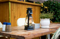 Street cafe table with old style petrol-lamp Stock Photos