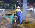 Street cleaner a pushing her trolley to crossing the road in the night in amoy city china Stock Photo