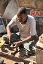 Street cobbler old delhi india april th a repairs shoes on the streets of Royalty Free Stock Images