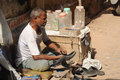 Street cobbler old delhi india april th a repairs shoes on the streets of Stock Photos