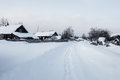 Street covered with snow in traditional russian village Royalty Free Stock Photo
