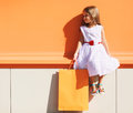 Street fashion kid, pretty little girl in dress with shop bag Royalty Free Stock Photo