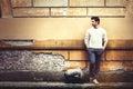 Street fashion model tourist man outdoor. Waiting on grunge wall Royalty Free Stock Photo