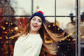Street fashion portrait of smiling beautiful young woman playing with her long hair. Lady wearing classic winter knitted Royalty Free Stock Photo