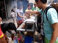 A street food vendor sells barbecue in a food cart along a street in Antipolo City, Philippines