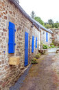 Street in the french brittany stone houses with blue windows on a cloudy day it s a vertical picture Stock Image