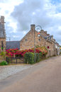 Street in the french brittany stone houses with red flowers on a cloudy day it s a vertical picture Royalty Free Stock Photos