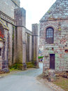 Street in the french brittany stone houses with romanesque church background are it is a vertical image on a cloudy day Royalty Free Stock Image
