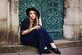 Street full body portait of stilylish smiling young woman sitting near the door. Model looking at camera. City lifestile Royalty Free Stock Photo