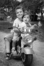 On the street hugging brother little sister they ride on a mot summer motorcycle black and white photo Stock Photography